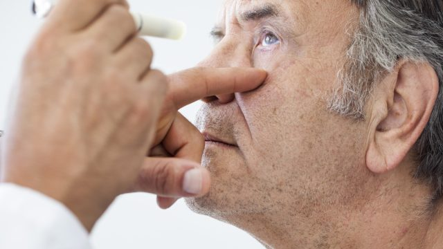 older white man getting his eye examined by a doctor