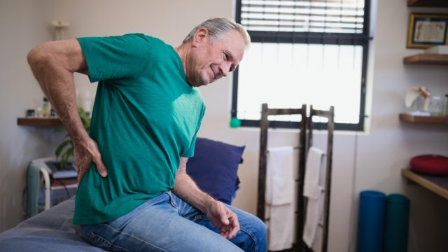 older white man with pain in side or back