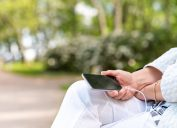 A senior woman with headphones is listening to music on her smart phone in the park