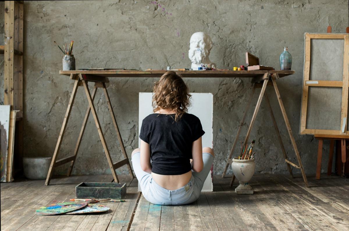 Woman painting sitting on floor