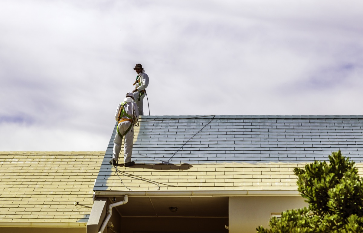 two men painting a roof