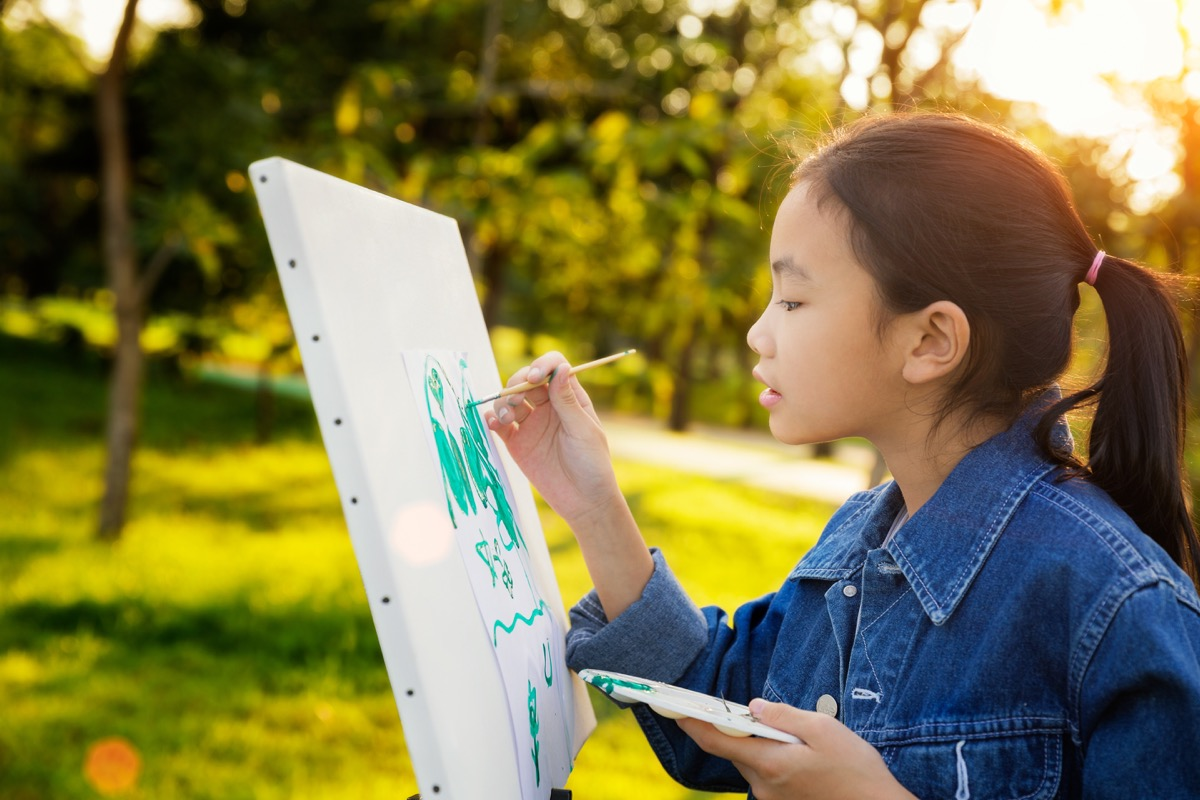 Young girl painting outside on a canvas