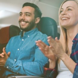 a young woman and man clap on a plane