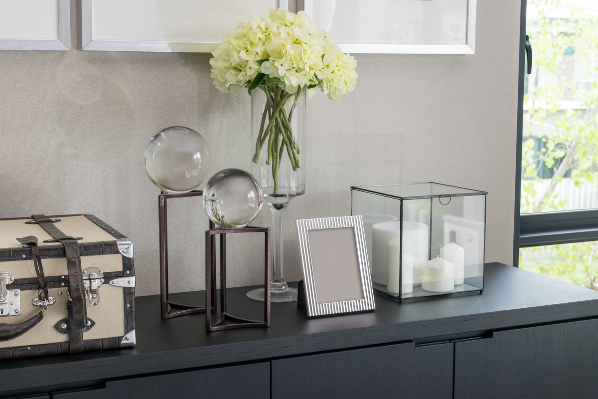 picture frames and candles on gray dresser