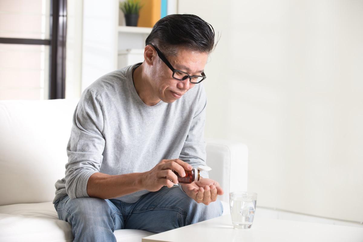 Man taking medication with water