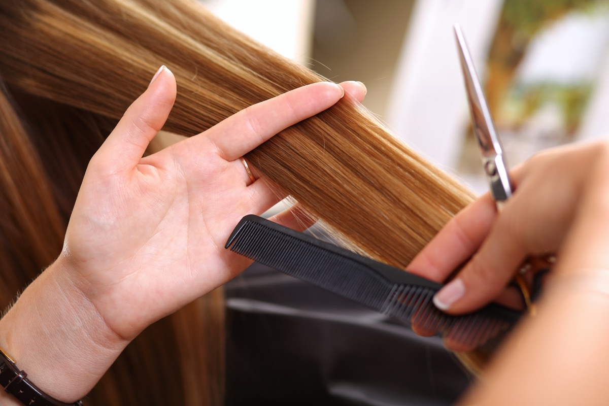 Female hairdresser hold in hand between fingers lock of hair, comb and golden scissors closeup. Hairdresser salon, barber shop, perfect look, new hairdo and color, straightening concept