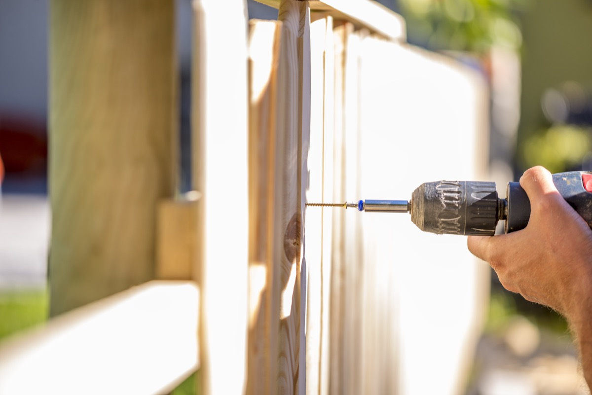 man putting a wooden fence up outside his home