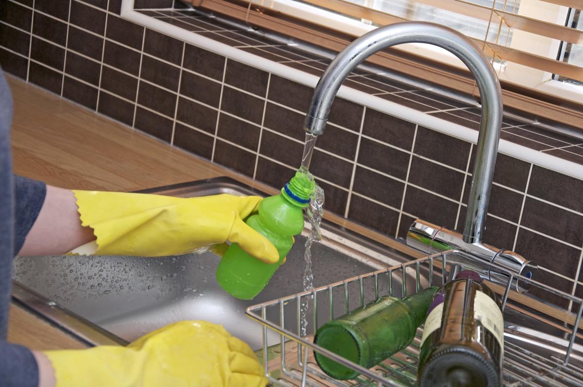 Rinsing recyclable bottle in sink