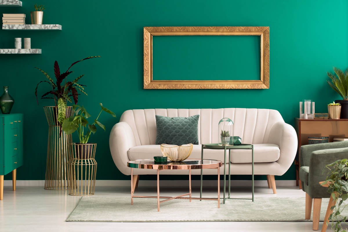 rounded beige sofa against green wall