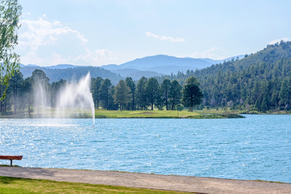 fountain in a blue lake with mountains in the background