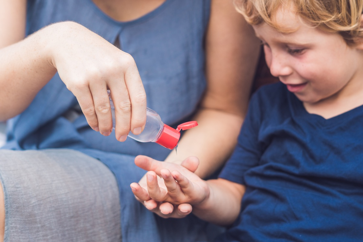 Mom pouring hand sanitizer in child's hand