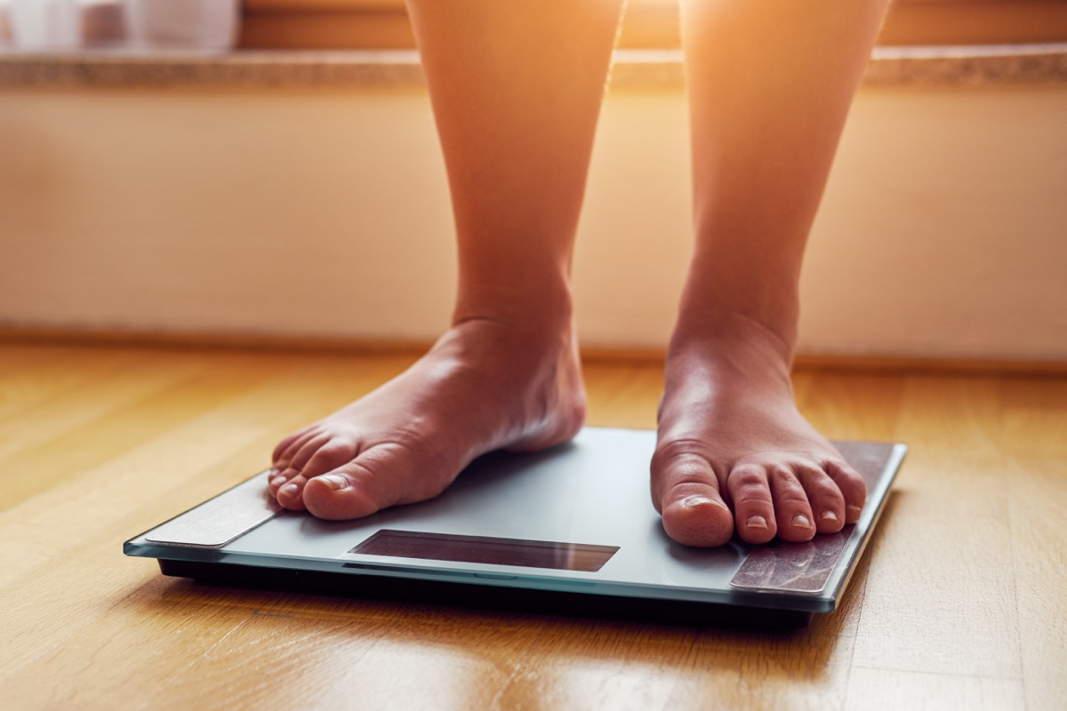 Woman stepping on a scale to weigh herself