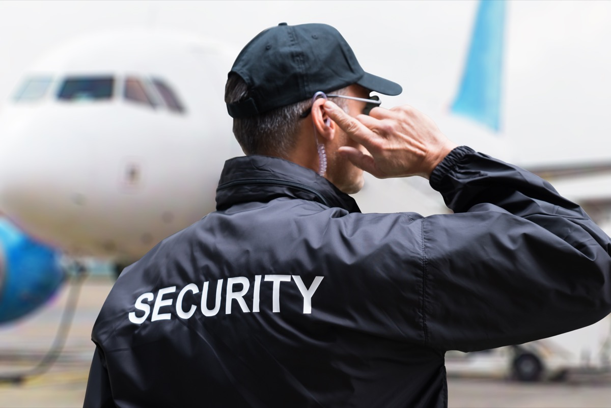 security personnel on the ground near an airplane
