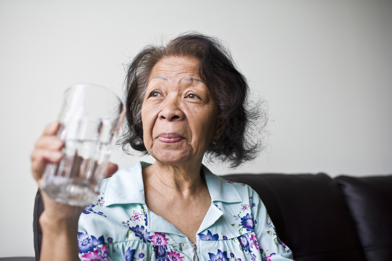 senior Asian Woman with a glass of refreshing water