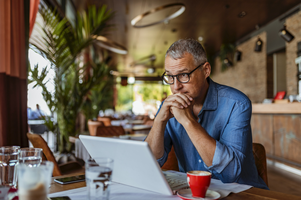 stressed middle aged man feeling sad at laptop