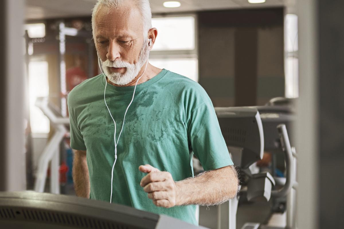 Senior man running on treadmill while listening to music