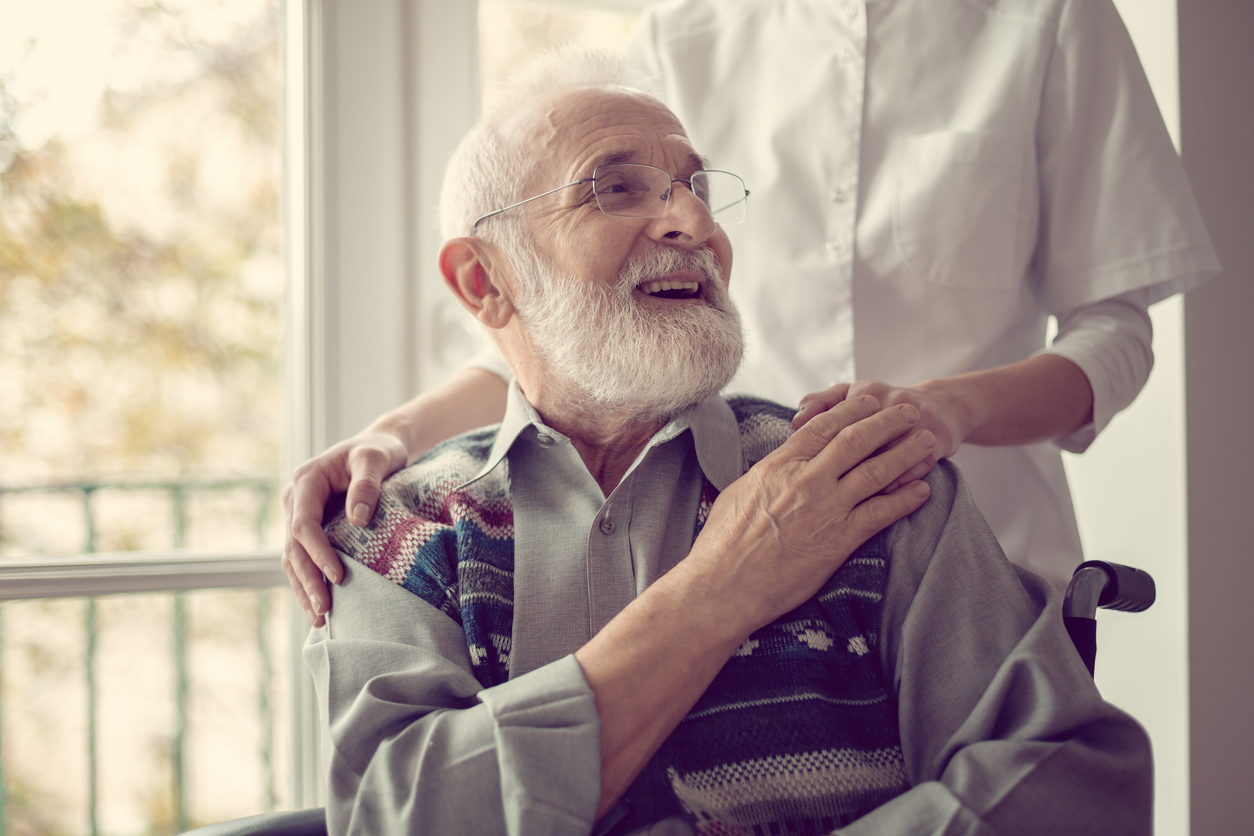 Senior man sitting in a wheelchair, laughing and holding his nurse's hand