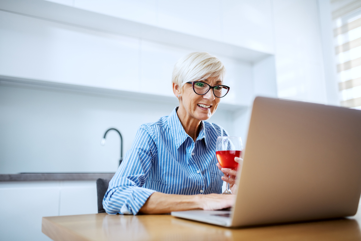Happy smiling white blonde senior woman sitting at dining table, drinking red wine and having video call over at laptop