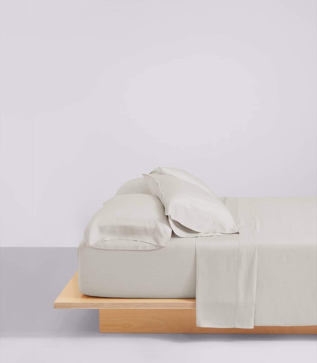 wooden platform bed with beige sheets