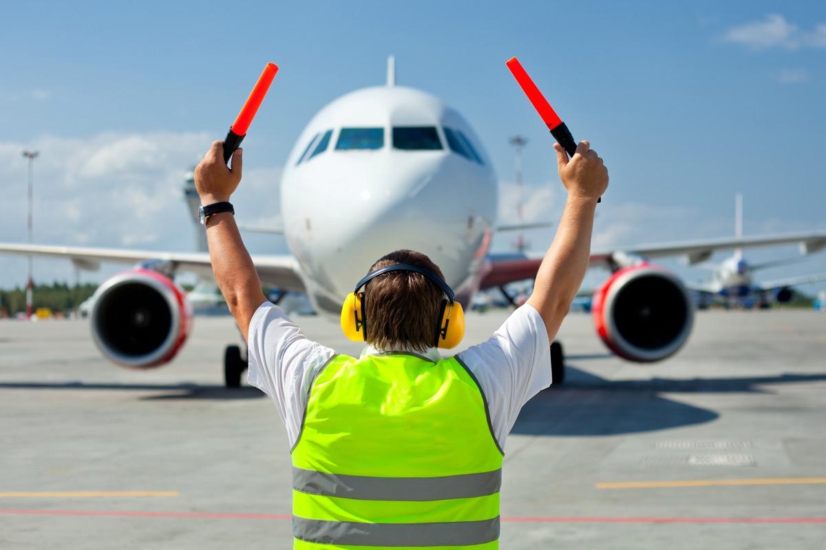 ground crew signaling to plane
