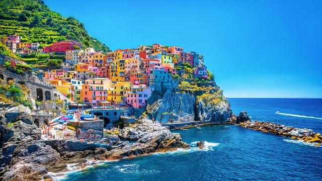 pastel colored buildings on a seaside cliff in italy