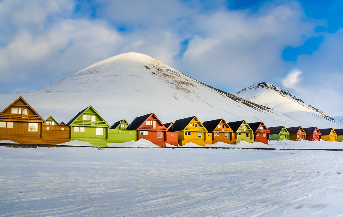 a row of colorful houses in a snowy landscape