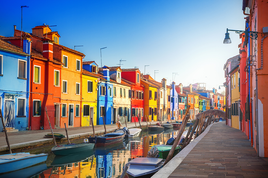 rainbow houses on a canal in burano, italy