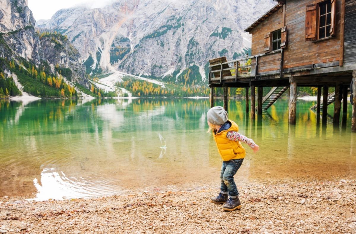 Little girl skipping stones on a beautiful lake