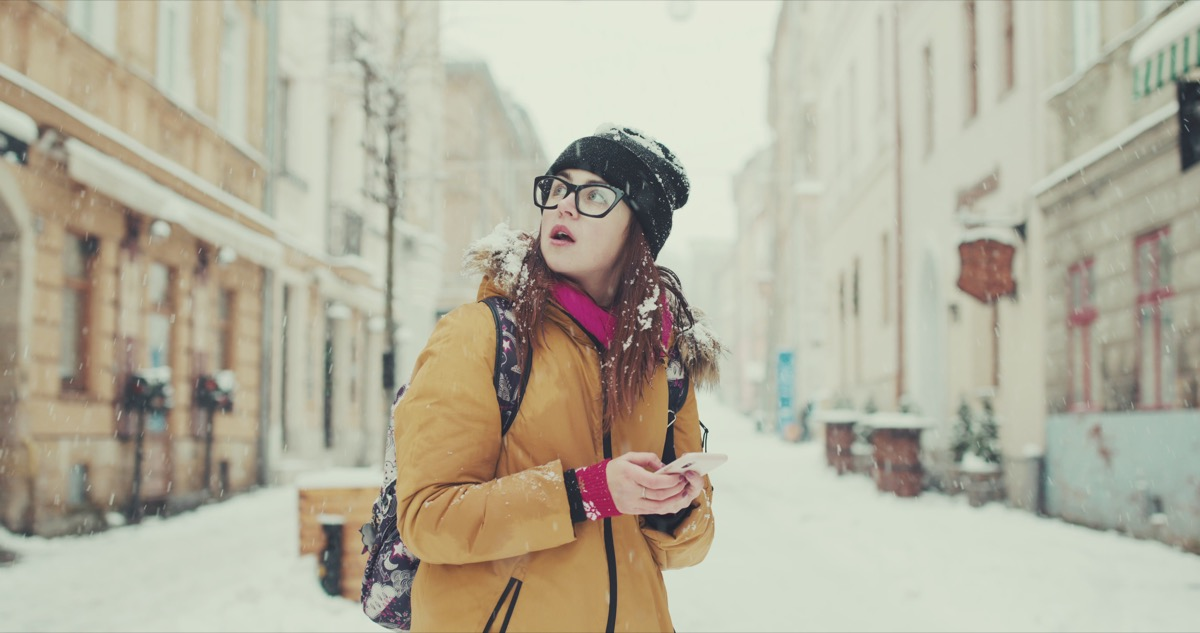 Woman confused lost walking through snow with phone