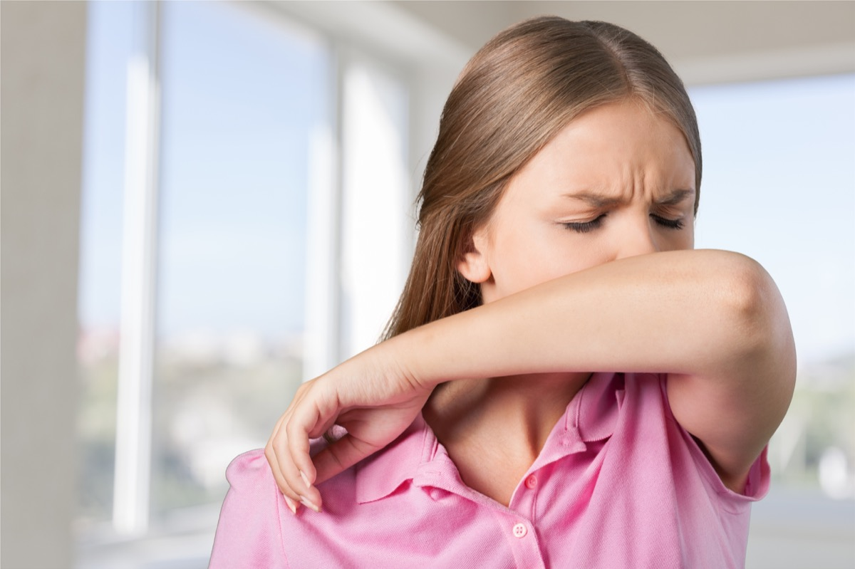 Woman sneezing or coughing into her elbow