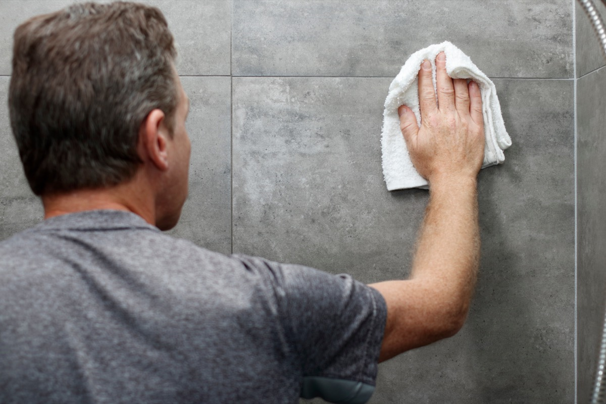 Man cleaning stone shower