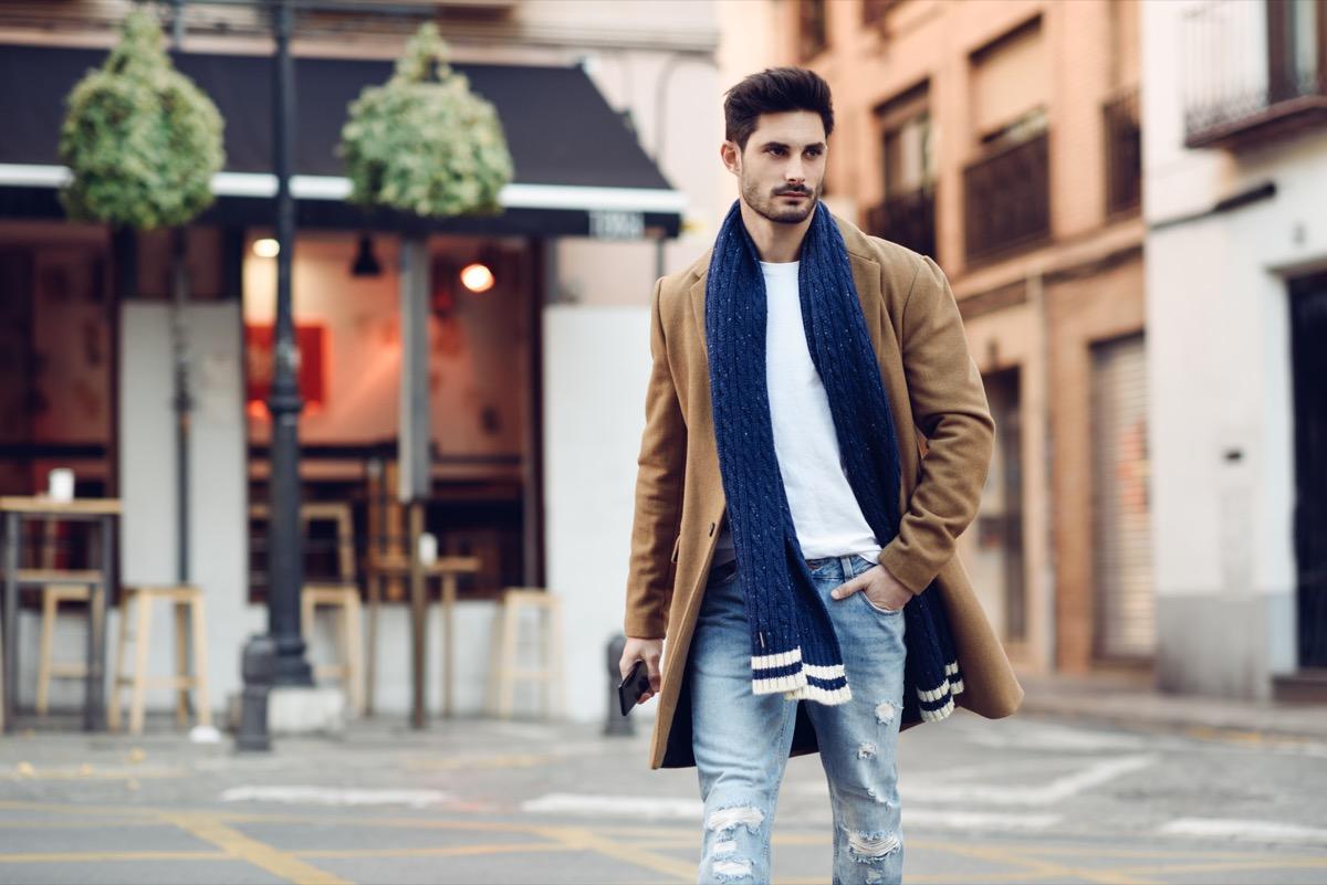 Stylish man walking across street