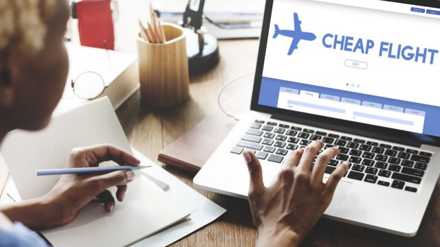 woman checking cheap flights on her laptop
