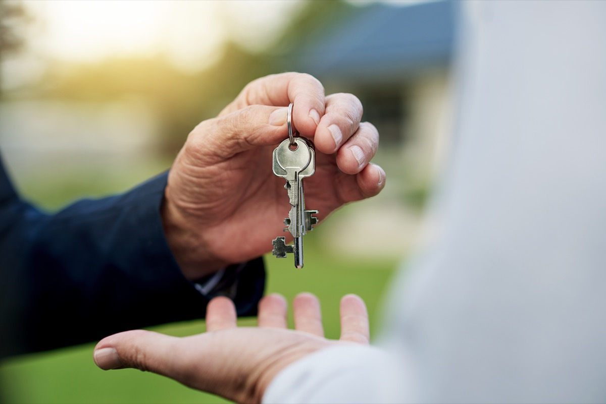 two hands handing over a key for property