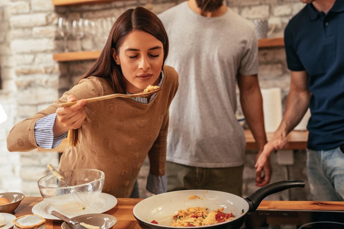 Woman tasting food she is making before seasoning