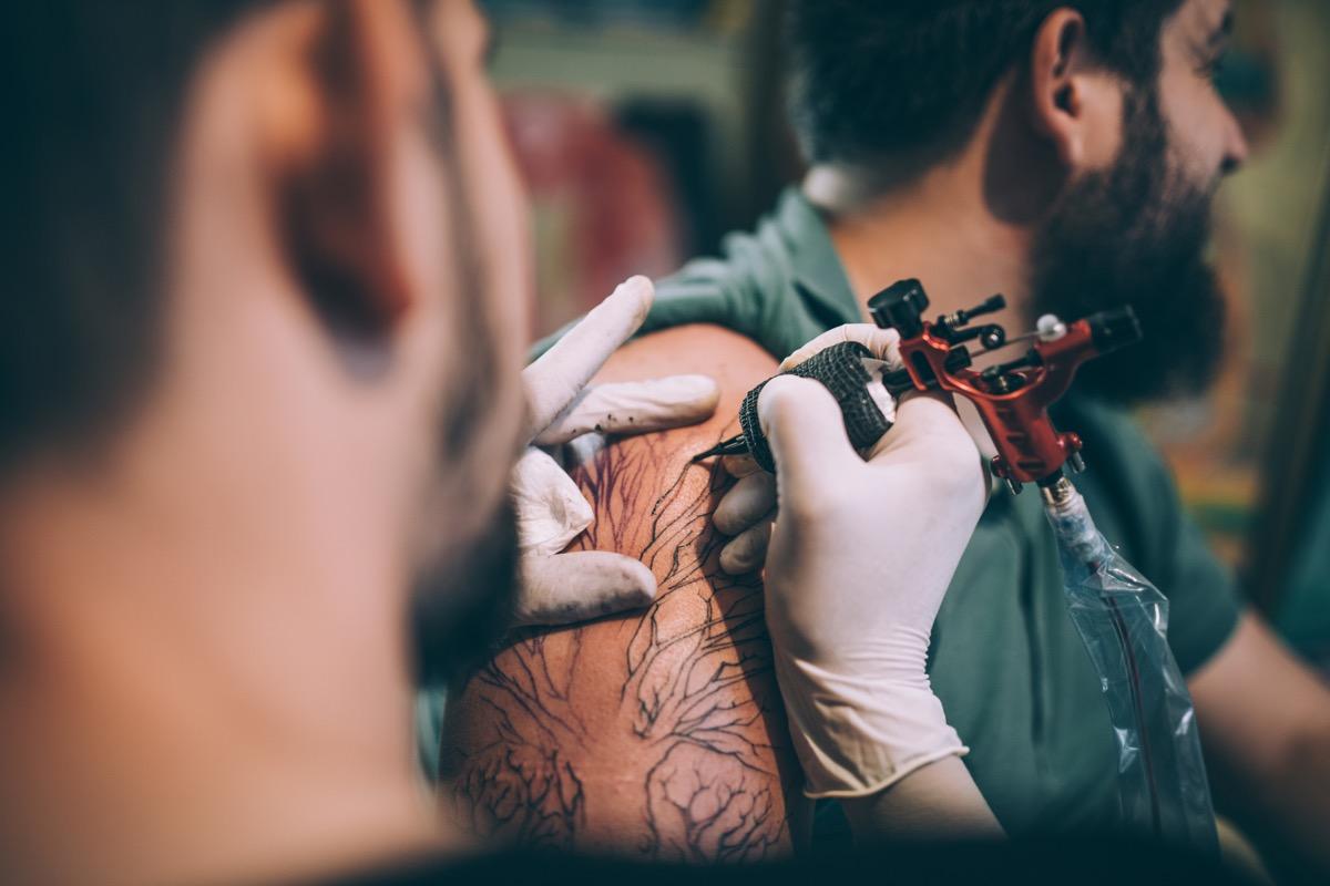 Two men, tattoo artist tattooing a man's arm in his tattoo studio.