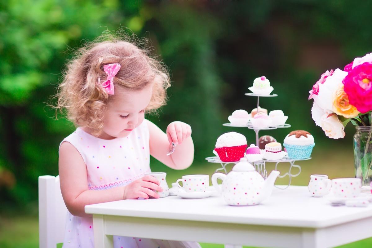 Little girl having a tea party outside
