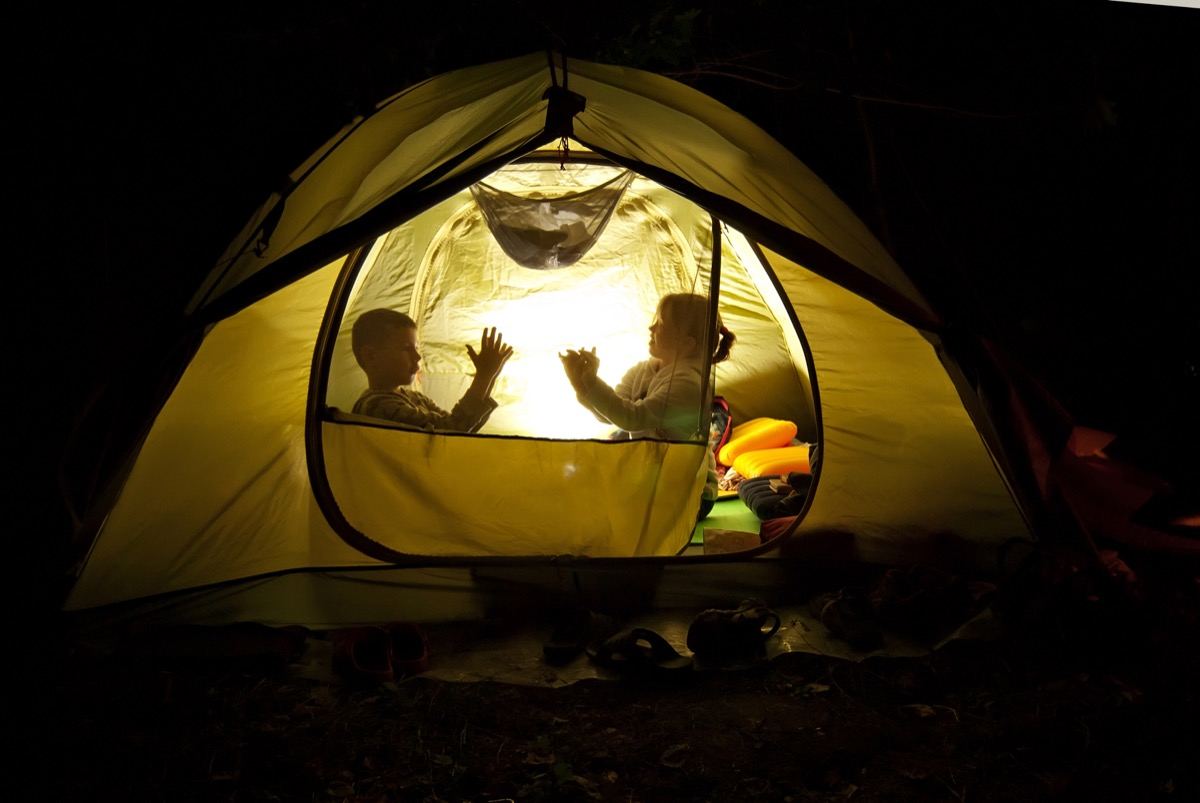 Kids camping in their backyard in a tent