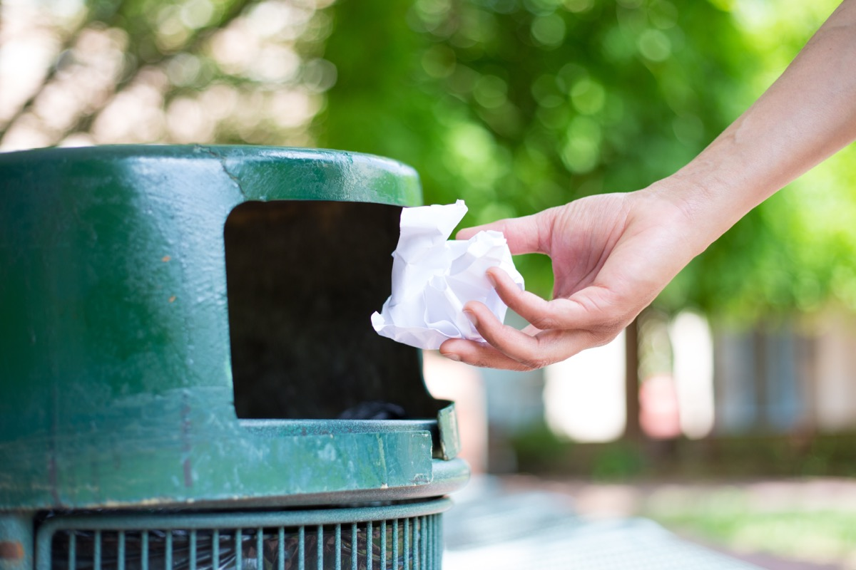 Person throwing away used tissue or paper