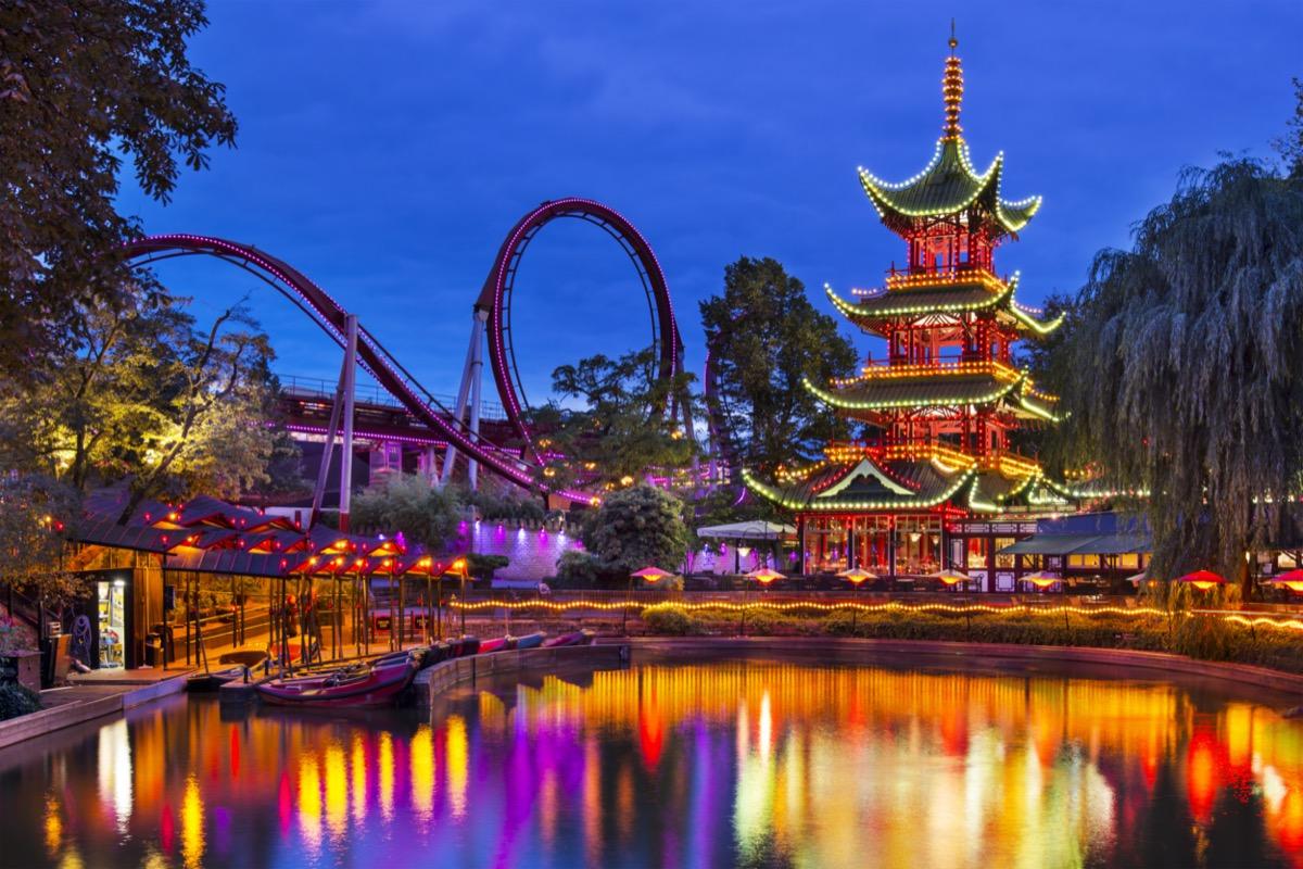 Evening view of Tivoli Gardens with a pagoda on the shore of pond and Daemonen roller coaster, Copenhagen, Denmark
