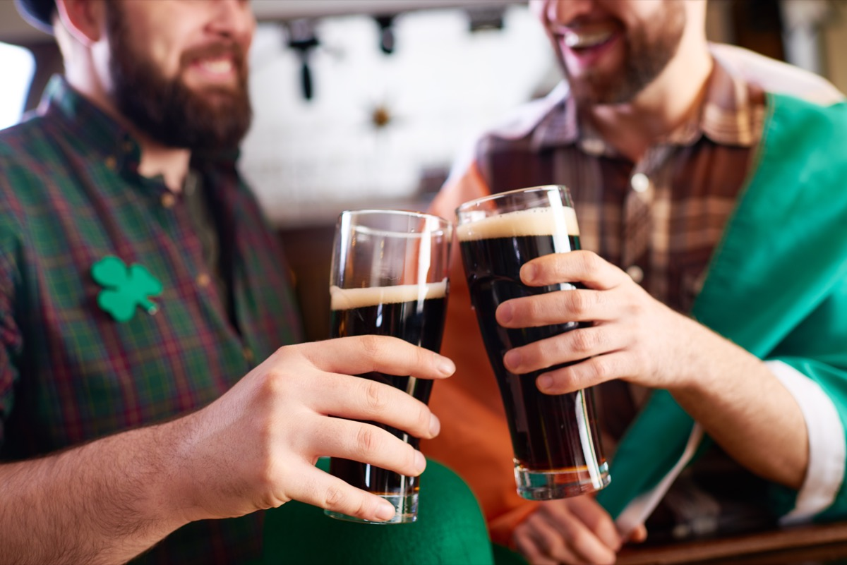 cheerful men in costume clinking beer glasses while celebrating St Patrick day