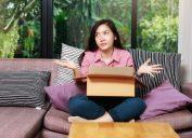 upset young asian woman opening box