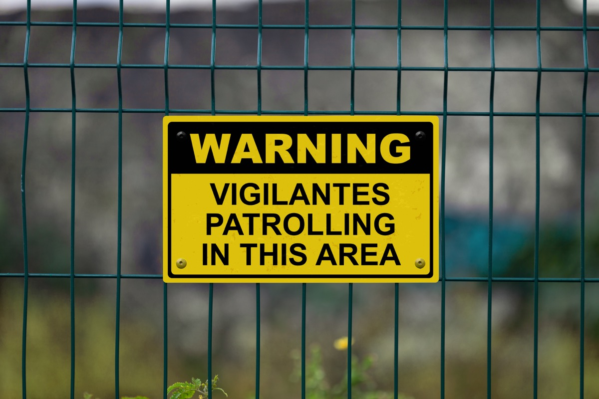 """Red an white warning sign on a fence stating in """"Warning - Vigilantes patrolling in this area"""" with a blank space underneath."""