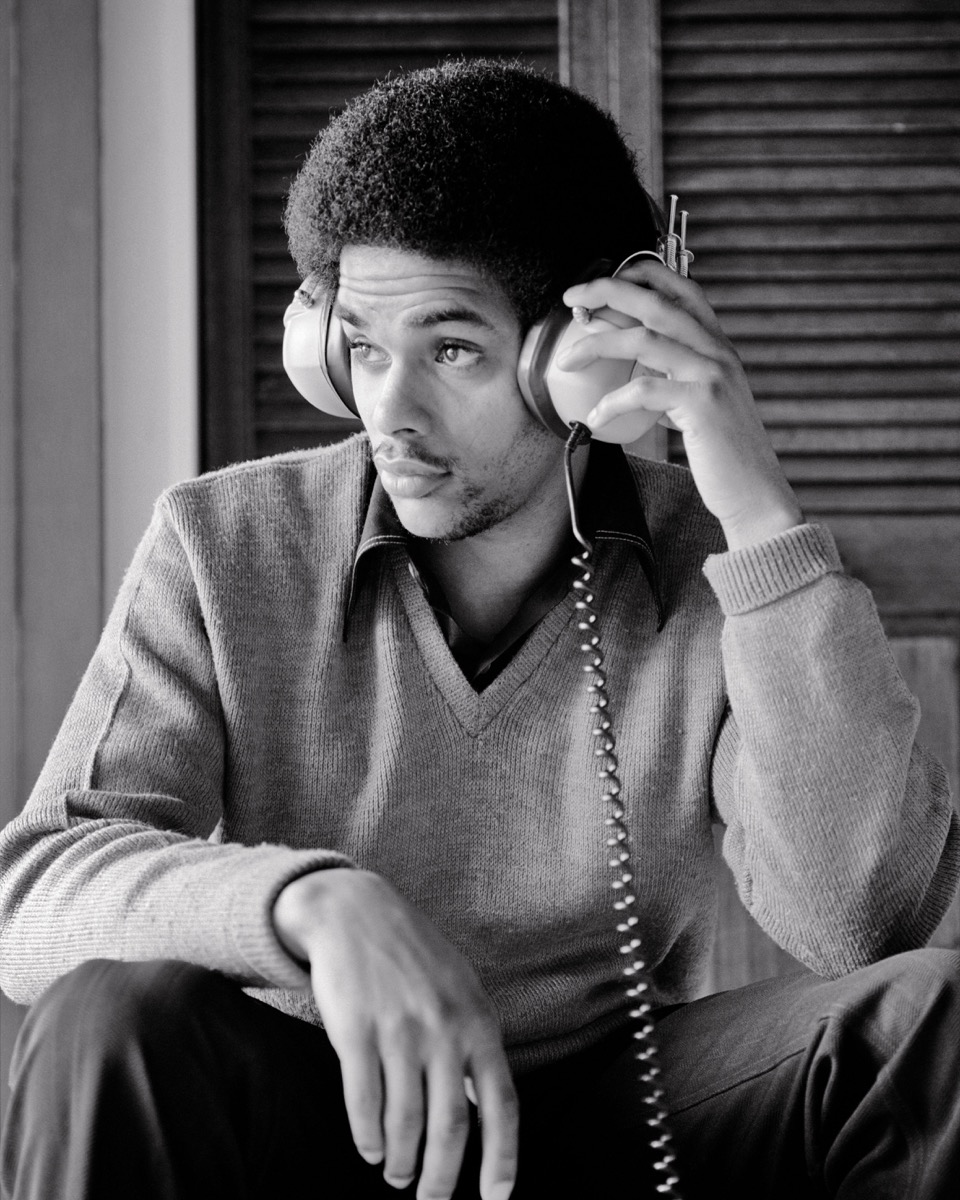 1970s AFRICAN-AMERICAN TEENAGE YOUNG MAN LISTENING TO MUSIC USING STEREO HEADPHONES