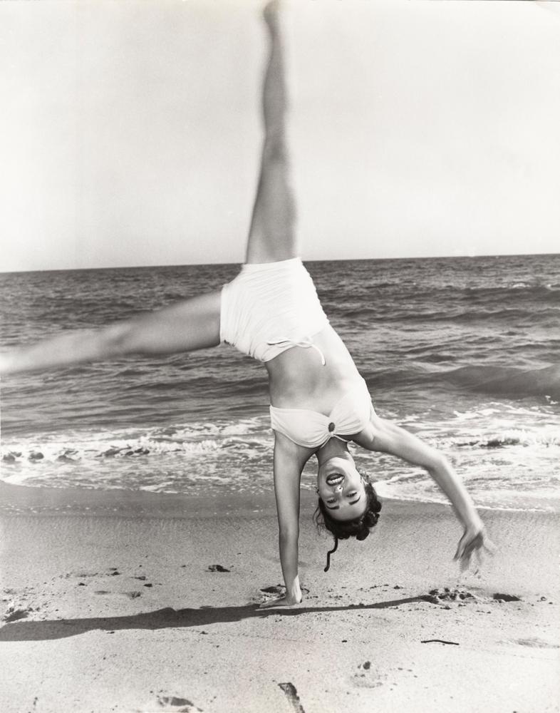 woman on beach doing cartwheel in bikini in 1940s