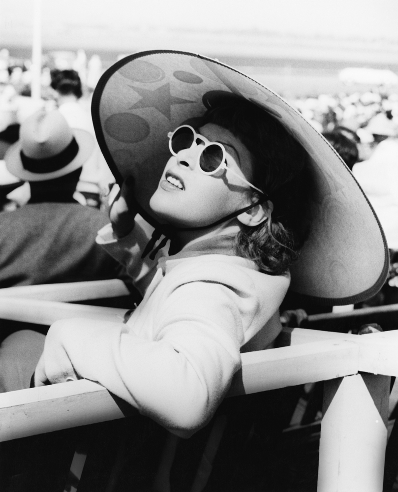 Woman in a big sun hat and sun glasses in 1940s