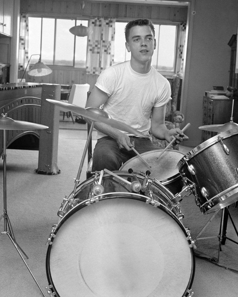1960s TEEN BOY WITH BUZZ CUT IN T-SHIRT SITTING IN FRONT OF SMALL DRUM KIT HOLDING STICKS OVER SNARE