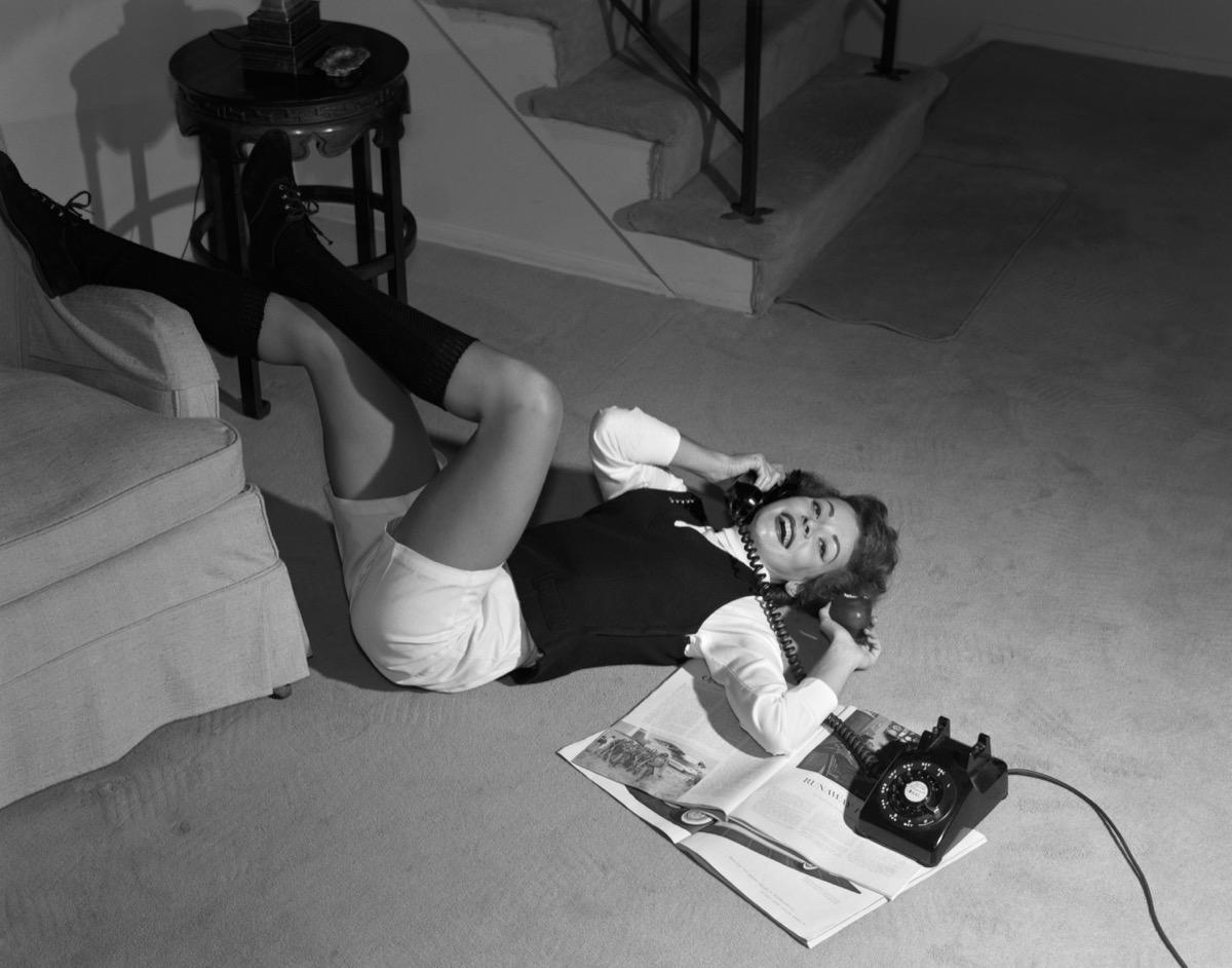 1960s TEEN GIRL LYING FLOOR WEAR SHORTS AND KNEE SOCKS, READING MAGAZINE & TALKING ON TELEPHONE