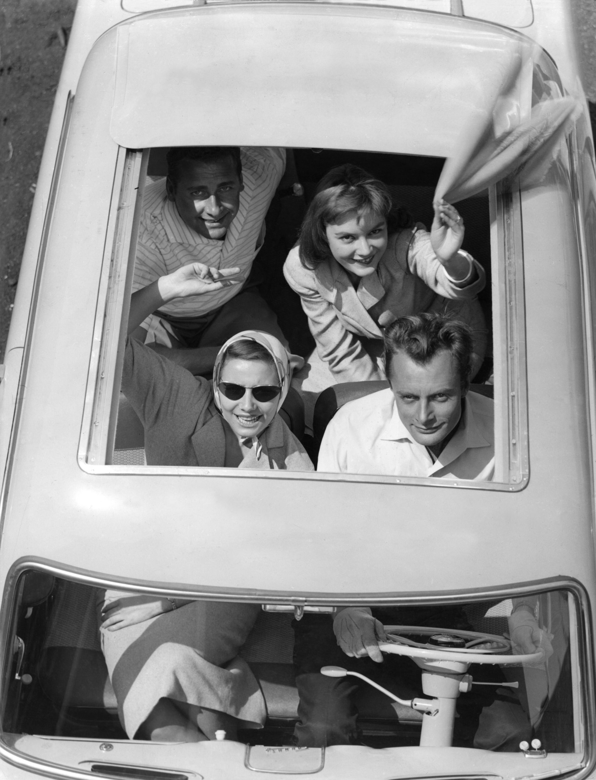 young people waving from open convertible top of car in 1950s