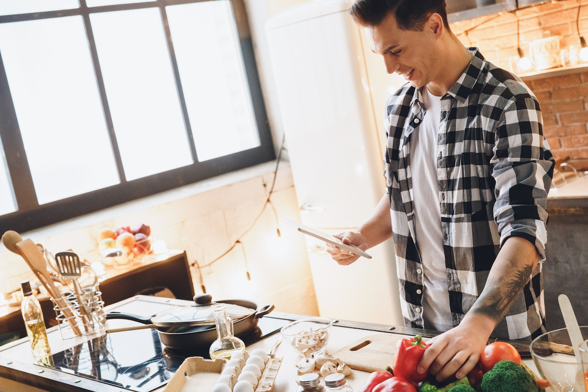 young adult man holding tablet smiling and cooking dinner